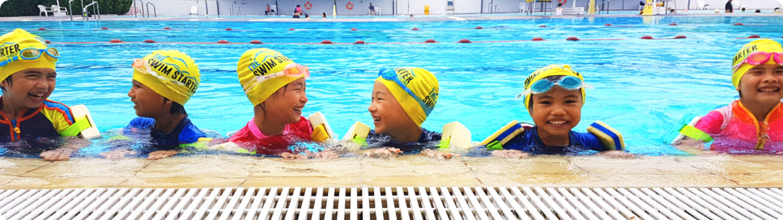 A group of happy children wearing safety Arm Floats, Yellow Swimming Cap and Goggles, are having their swimming lessons in the deep pool