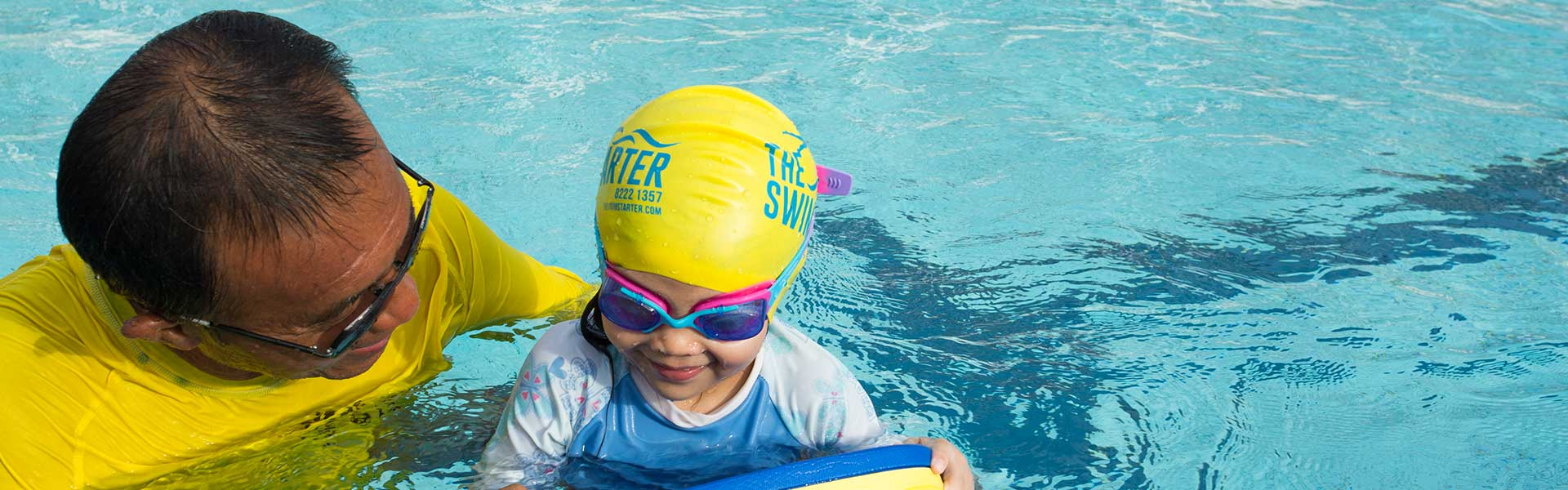 Swimming pool training for child by balancing in deep pool                  using a float with coach supervision